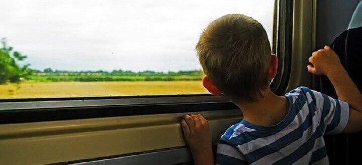 Мальчик смотрит в окно в поезде
